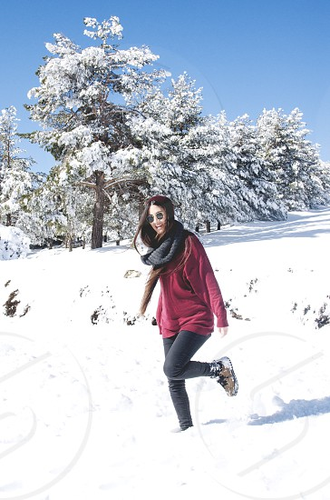 Young brunette woman with sunglasses and red sweater having fun and laughing in the snow in SierraNevada Almeria-Granada Andalusia Spain photo