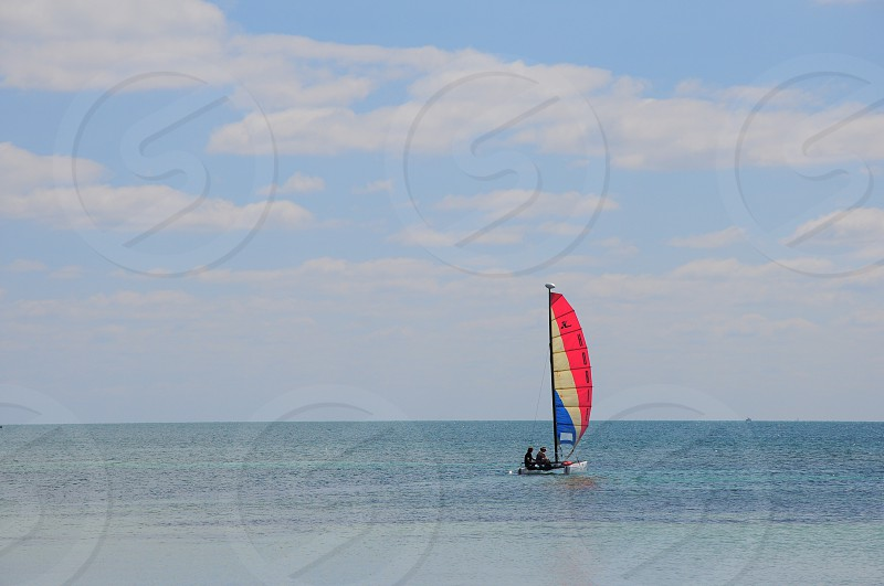 2 people riding red white and blue sailboat sailing on blue ocean water under blue and white sunny cloudy sky photo