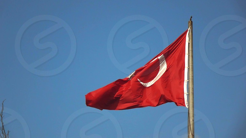 Waving national flag of Turkey on a background blue sky. A red flag featuring a white star called as moon-star. Slow motion Full HD video 240 fps 1080p. photo