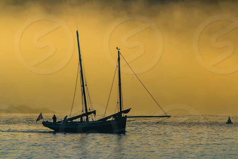 Ketch heading out to sea at sunrise on a misty day photo