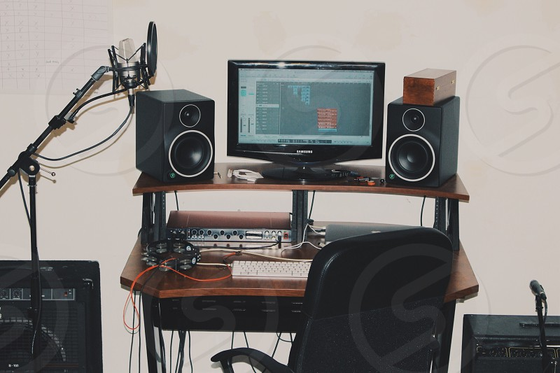 turned on flat screen computer monitor speakers and keyboard on top of brown wooden computer desk photo