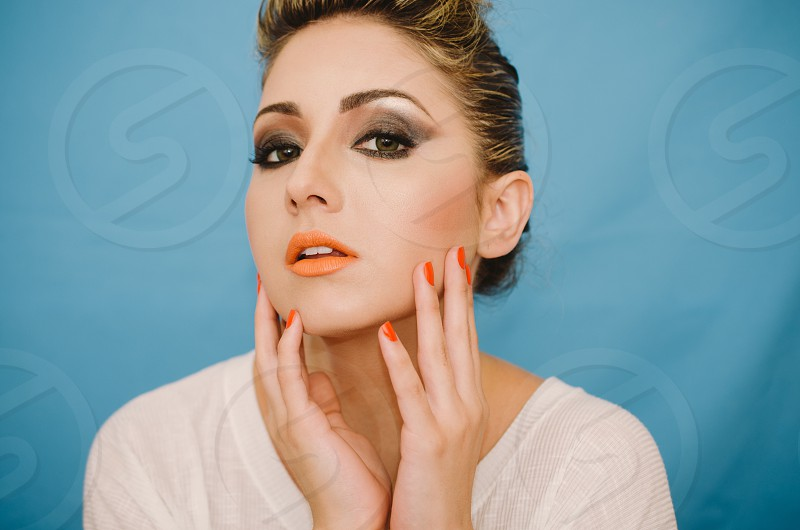woman with orange manicure and orange lipstick wearing a white scoop neck shirt photo