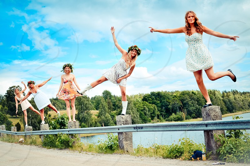 girls standing on fence posing photo