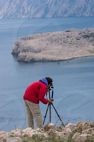 Man in bright red jacket photographing sea and island rocky landscape using camera on tripod photo