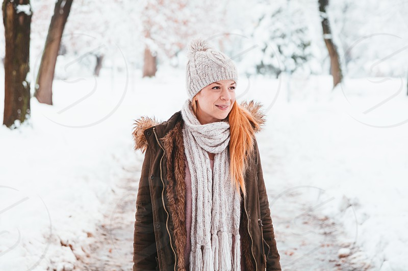 Young woman walking in the park on a snowy day photo