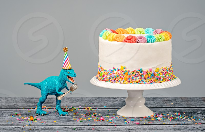 Hungry toy dinosaur wearing a hat and holding a fork next to a birthday Cake on a gray background photo