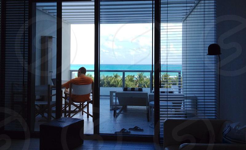 Man wearing a orange shirt sitting on the patio photo
