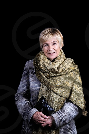 Portrait of an elderly woman in a draped coat with a thrown shawl on her shoulders and a clutch bag. Black background. photo
