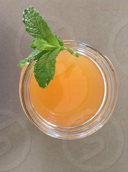 clear drinking glass filled with yellow liquid with mint photo