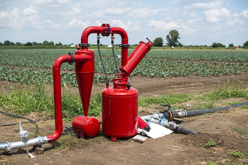 Water pump and pipes on farmland. Agriculture and watering concept. photo
