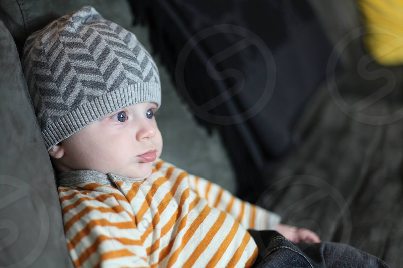 baby wearing stripe long-sleeved top and gray herringbone knit cap sitting in suede cushion photo
