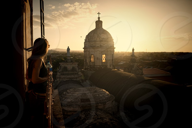 Lucky me. A beautiful view and a beautiful girl. While exploring we found ourselves in the right spot at the right time; just as the sun was setting behind a tower on the West end of Iglesia Merced in Granada Nicaragua. photo