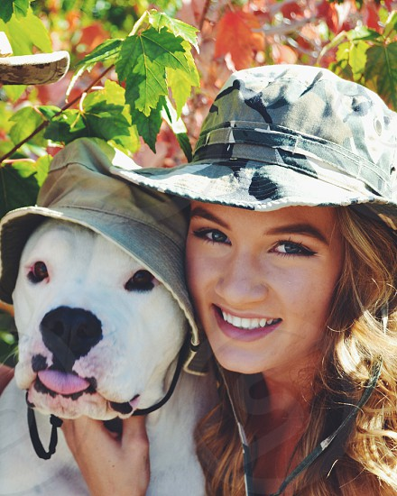 woman in camouflage hat holding white dog near tree during daytime photo