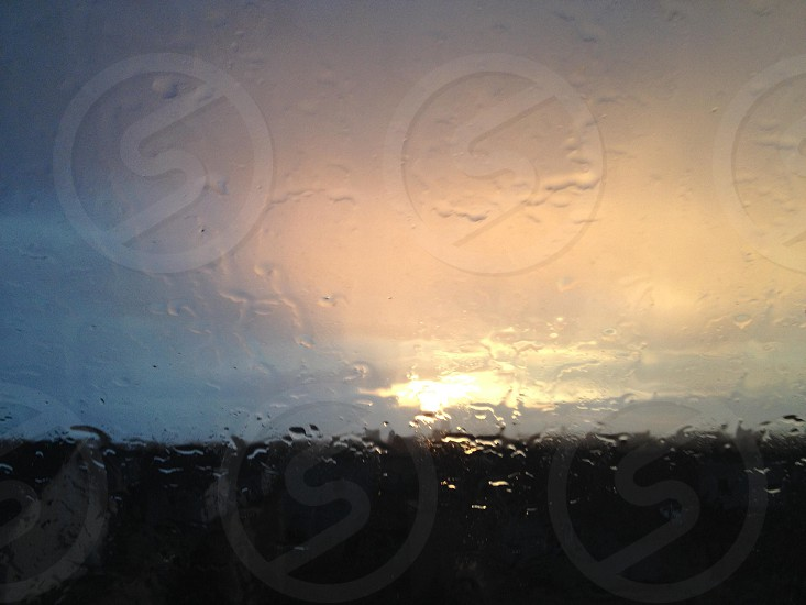 rain drops on clear glass window looking towards cloudy sunset photo