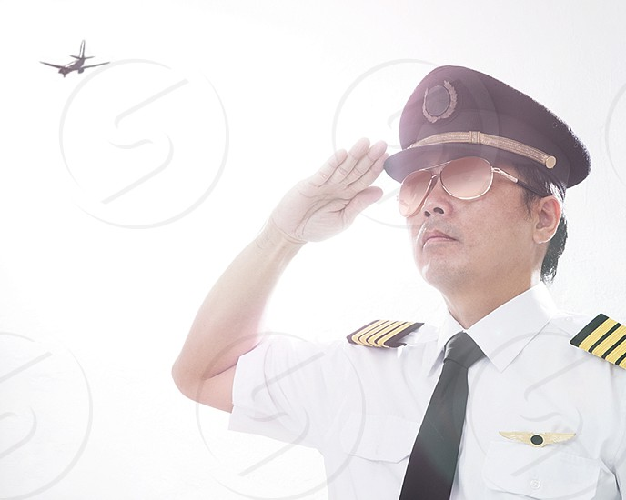 Portrait of an airline pilot giving salute gesture photo