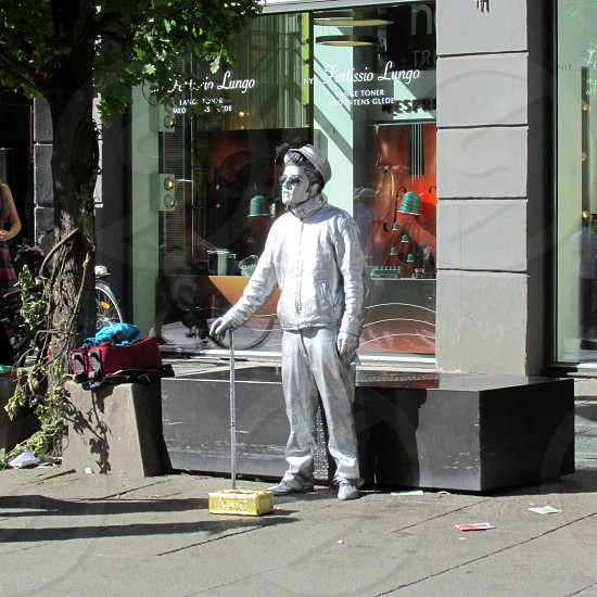 man in silver jacket and silver pants statue street performer photo