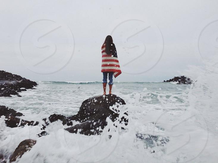 woman on rock near sea photo