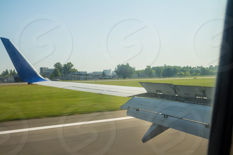 Airplane wing during landing with flaps down on the runway. photo