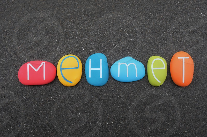 Mehmet turkish male given name composed with multi colored stone letters over black volcanic sand photo