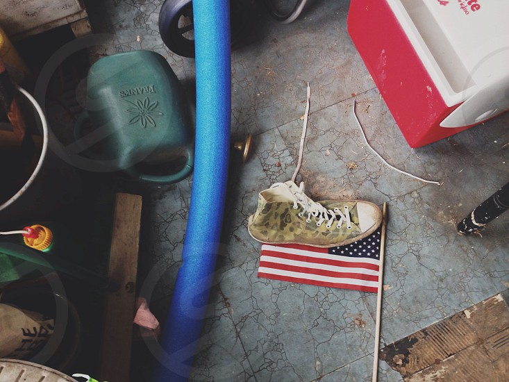 Classic American suburban porch American flag decaying floor tile warm dirt on the floor. photo