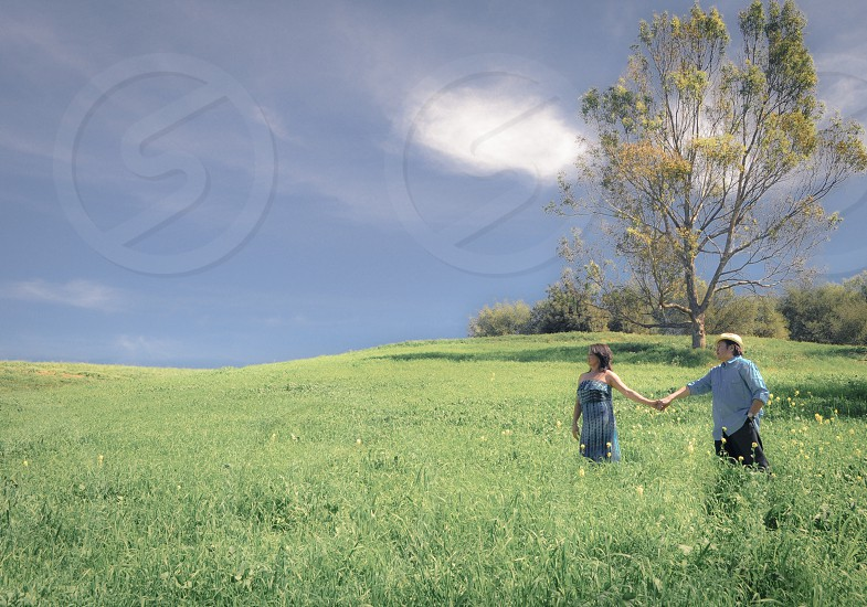 couple holding hands on grass photo