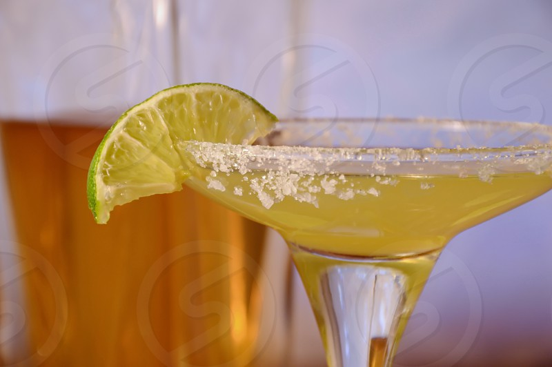 Tequila in a bottle and A margarita in a glass with lime wedge photo