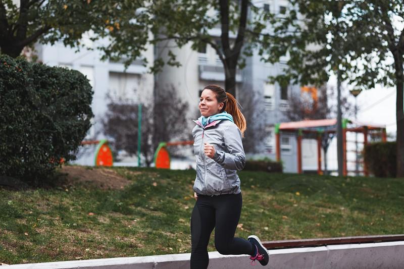 Woman running. Female runner jogging training for marathon. Fit girl fitness athlete model exercising outdoor. photo