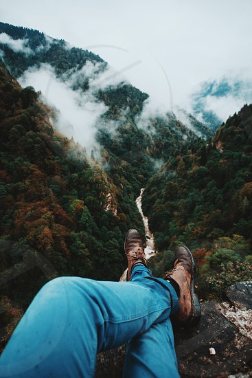 man in blue pants sitting on cliff facing trees on mountain and river during daytime photo