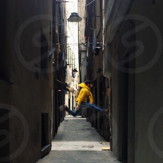 man in blue jeans yellow hooded jacket jumping up in alley surrounded by buildings photo
