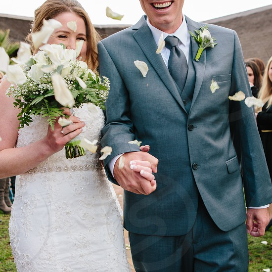 wedding couple confetti happy marriage laughter smile holding hands bouquet flowers bride groom bridal nuptials ceremony forever promise love photo