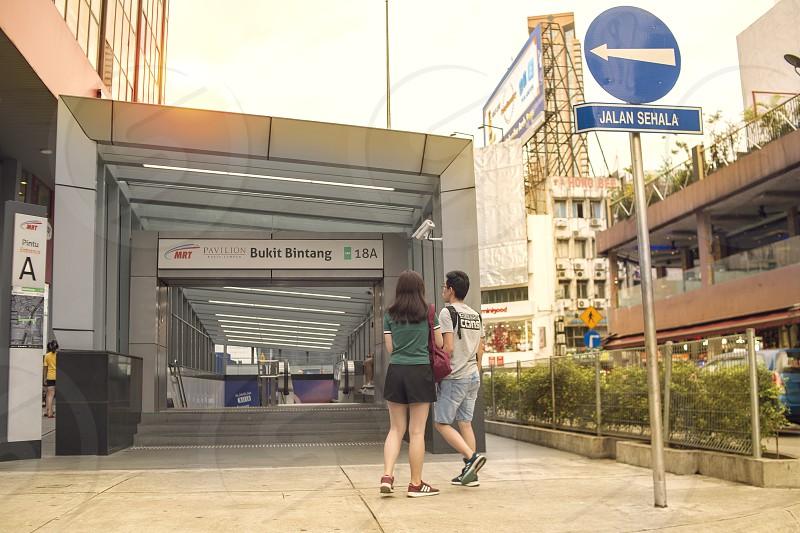tourists walking around bukit bintang area near a mrt entrance photo