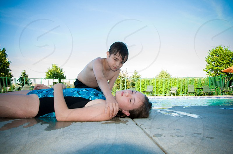 kid holding a woman wearing black and blue swim suit photo
