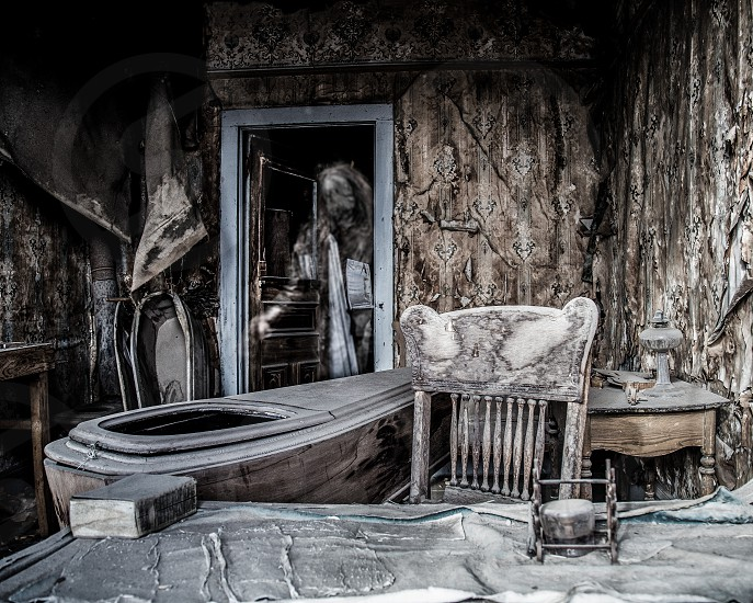 Ghostly figure entering an abandoned and decaying room filled with coffins. Ghost town. photo