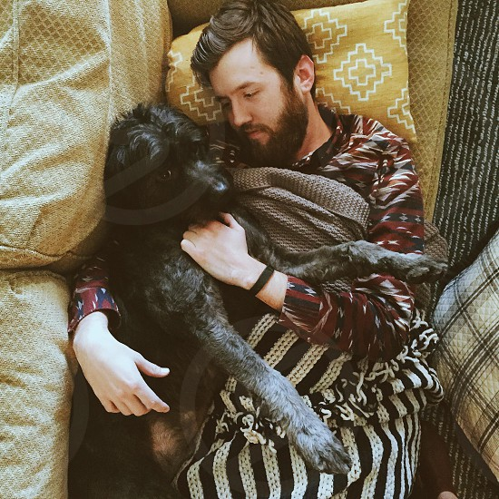 man on black and white stripe blanket hugging his black dog photo