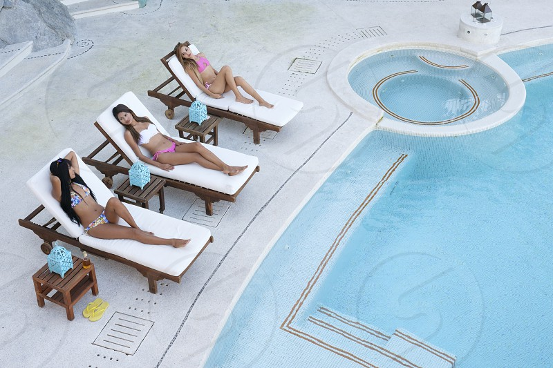 Three young attractive hispanic women using loungers for tanning next to swimming pool photo