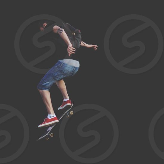 man in blue denim shorts playing a black skateboard photo
