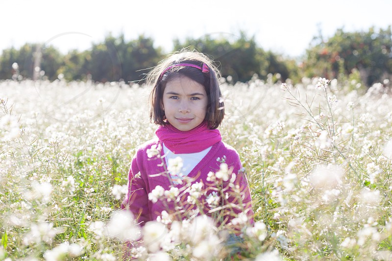 Girl in pink in a white flowers field. Outdoors.  photo