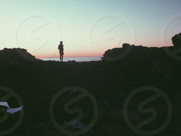 man on a cliff silhouette photo