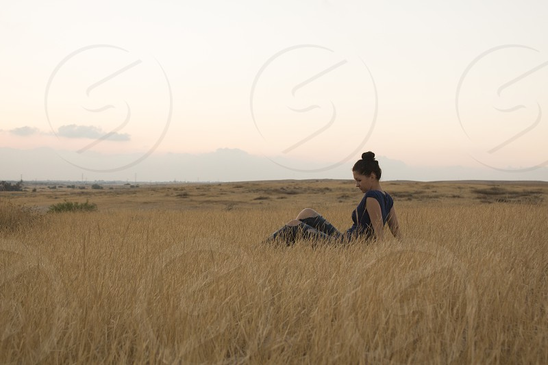 woman in black top sitting on brown leafed grass during daytime photo