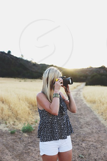 woman in black and white dotted blouse taking picture photo