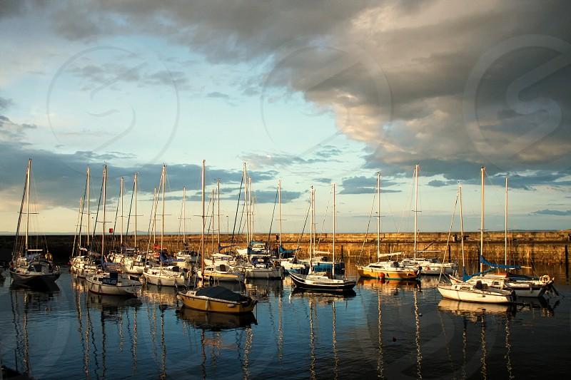 Sail boats anchored in small harbor at sunset. photo