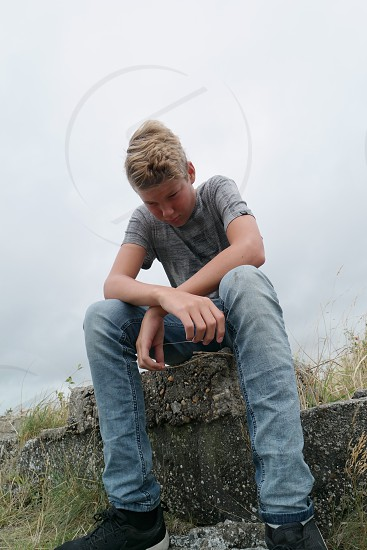 boy wearing gray top and blue jeans sitting on concrete bench photo
