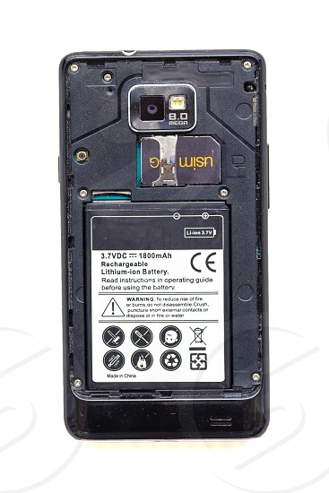 Back view of old smartphone with open cover isolated on white background. The battery and sim card are visible. photo