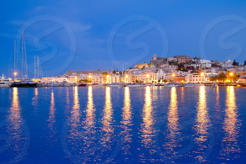 Ibiza island night view of Eivissa town and sea lights reflection photo