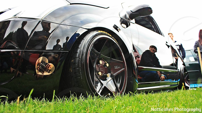 Modified car on cool black wheels at an automotive event photo