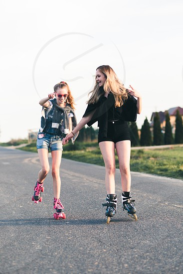 Teenage smiling happy girls having fun rollerskating together on summer day photo