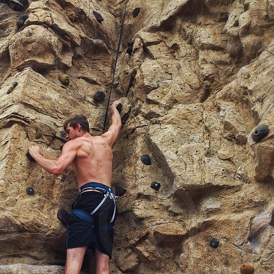 topless man wearing dark blue shorts and climbing harness scaling a rock wall photo