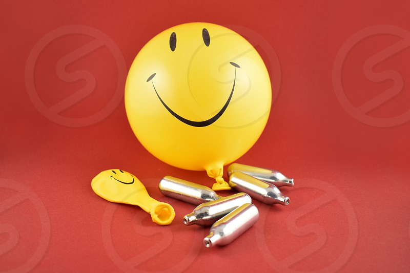 Laughing gas bombs. Laughing gas balloons. Happy emoji balloon. Smiley inflatable balloon isolated on a red background. Laughing party balloon. Nitrous oxide bulbs photo