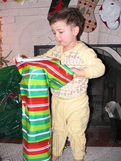 boy unwraps present in front of stockings photo