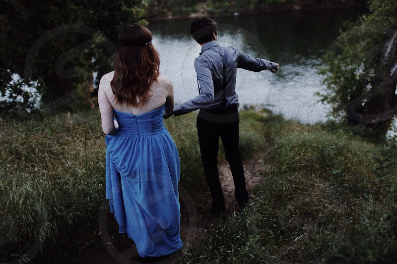 woman in blue strapless gown and man in grey button down shirt standing by a river photo